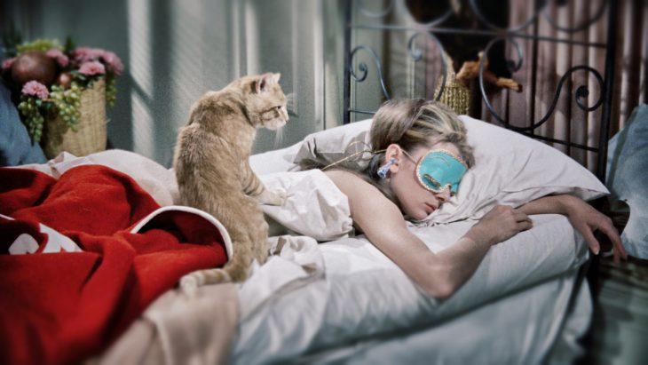 Mujer dormida con un gato naranja arriba de su espalda