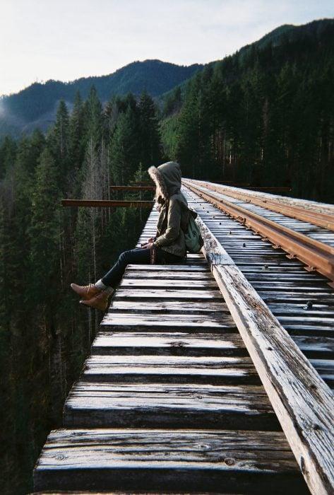 chica sentada a gran altura en las vías del tren