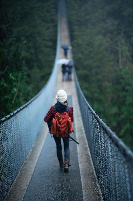 chica con equipaje caminando sobre un puente