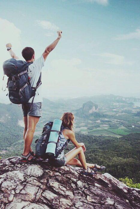 Pareja cargando equipaje al filo de una montaña