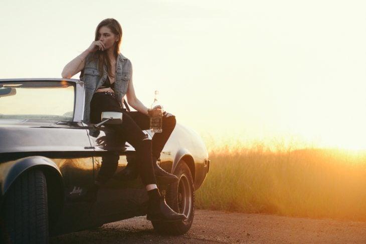 mujer femenina pero ruda en un carro a través de una puesta de sol