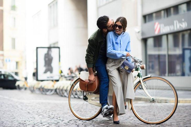 Pareja de novios en una bicicleta dándose un beso