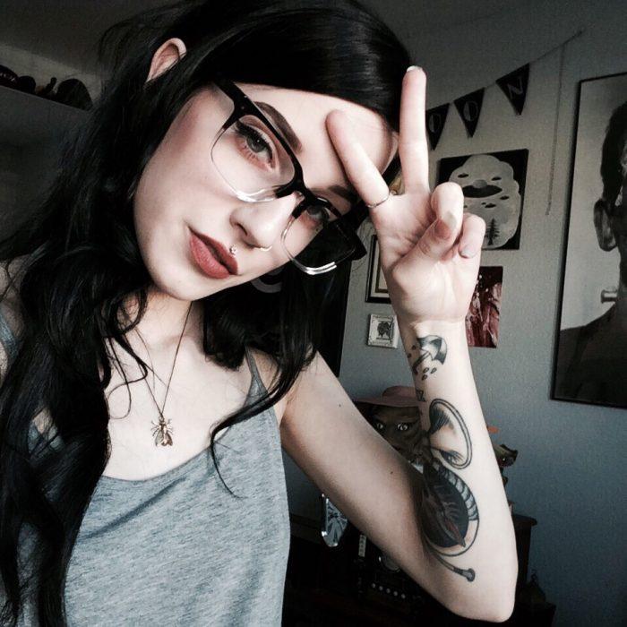 Chica de cabello negro y lentes con tatuaje