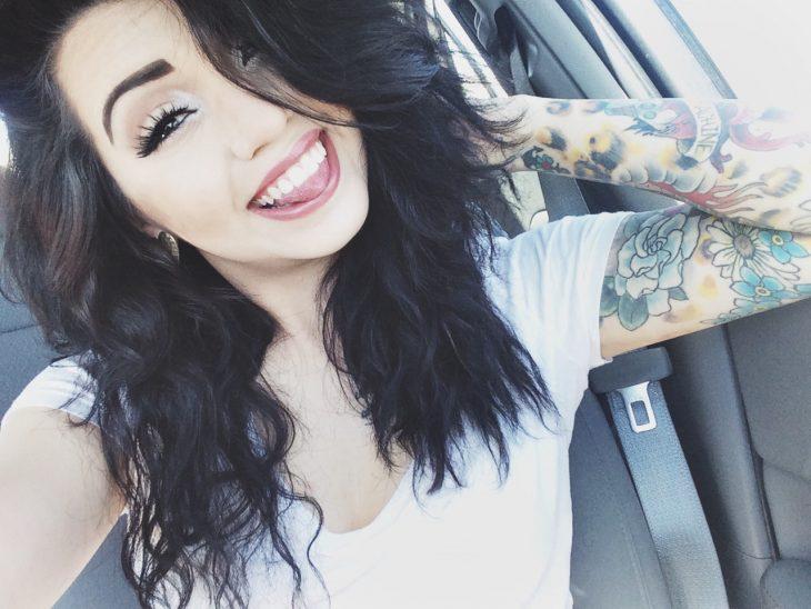 Chica sonriendo con un brazo tatuado