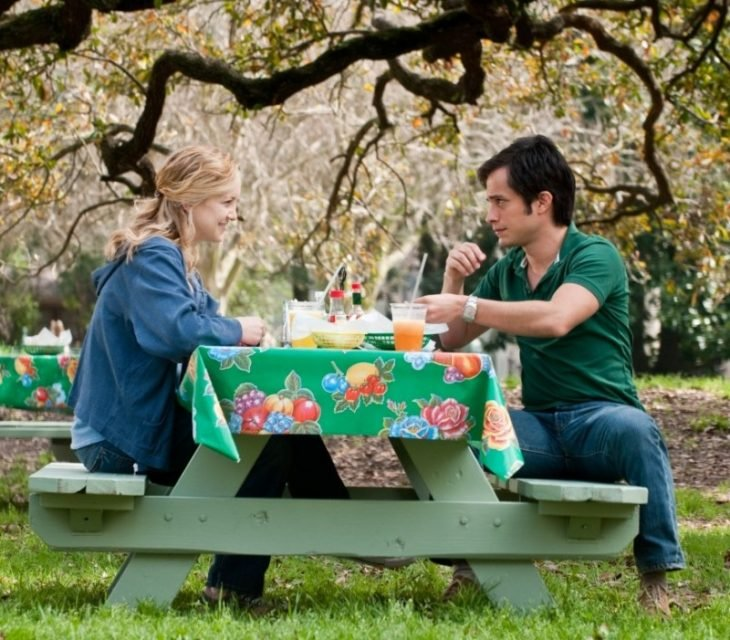 Pareja de novios al aire libre sentados a la mesa comiendo y viéndose frente a frente