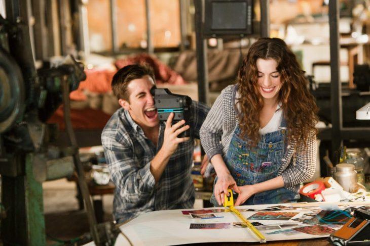 Hombre filmando con una cámara a su novia trabajando