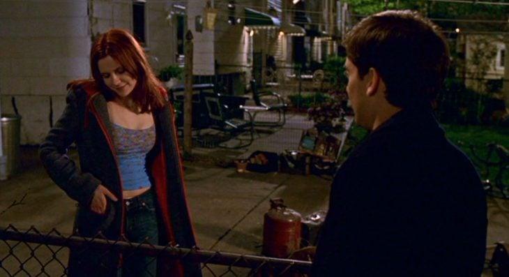 Un chico y una chica platicando por la noche fuera de su casa