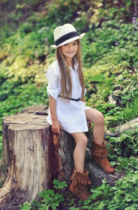 Kristina Pimenova posando para la cámara con un bluson blanco y sombrero