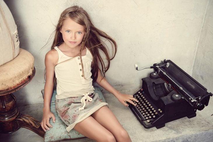 Kristina Pimenova posando con una maquina antigua de escribir
