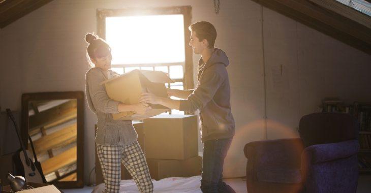 Pareja de novios mudándose juntos y cargando una caja