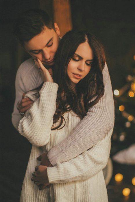 Pareja de enamorados abrazándose con los ojos cerrados