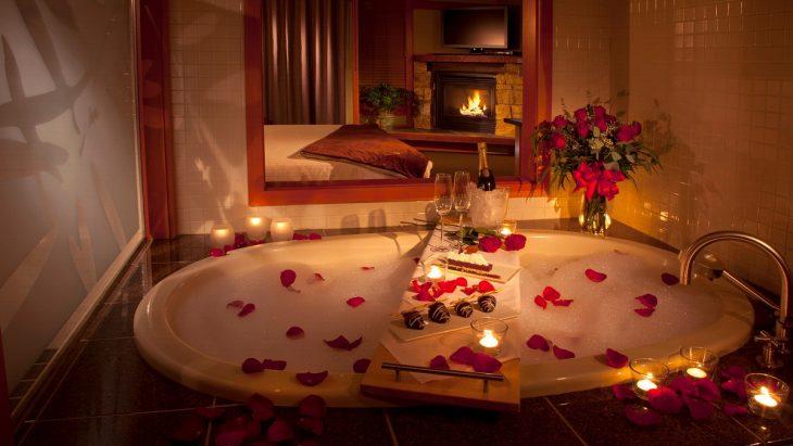 Bañera con pétalos de rosa, iluminada con luces de velas