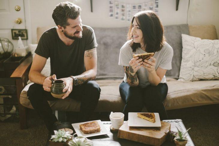 Pareja con tatuajes comiendo en un sofá