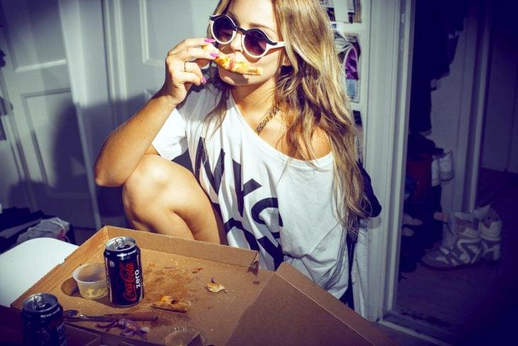 Chica comiendo pizza con una coca cola zero