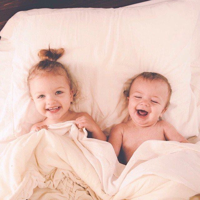 Hermanos pequeños acostados en la cama sonriendo