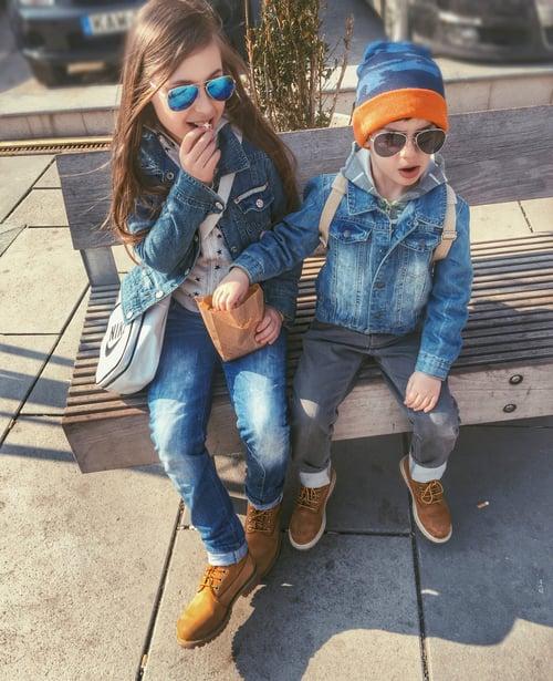 Hermanos vestidos similar comiendo palomitas en una banca