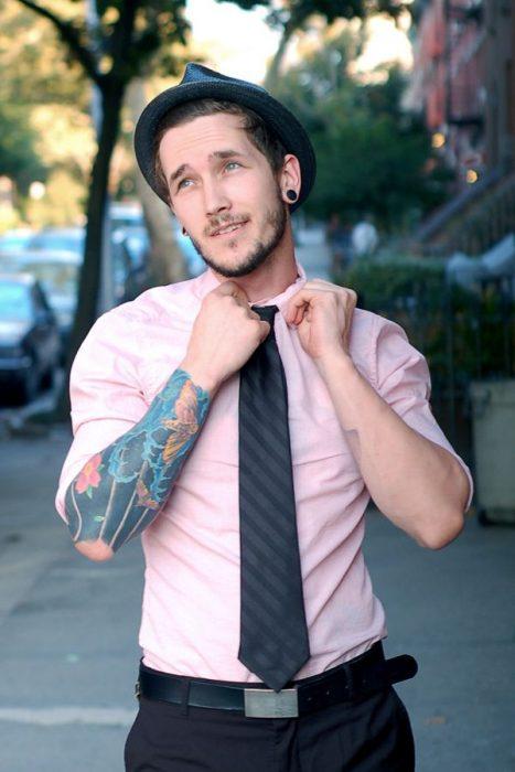 hombre de camisa rosa y tatuajes