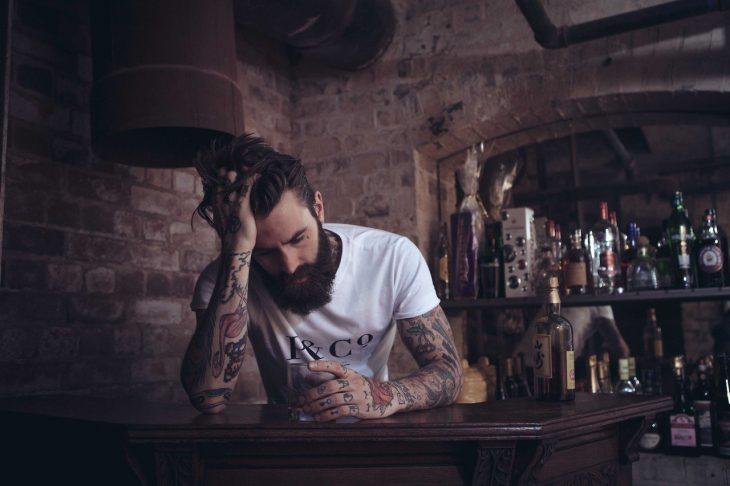 Hombre sentado en la mesa de un bar con tatuajes en los brazos