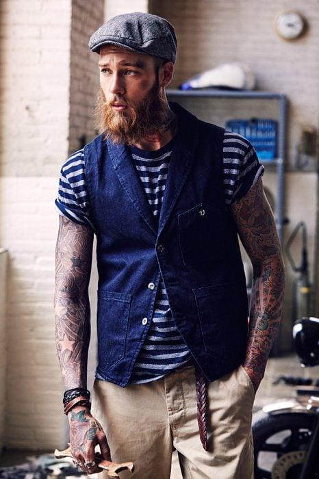 Hombre con tatuajes agarrando una llave inglesa