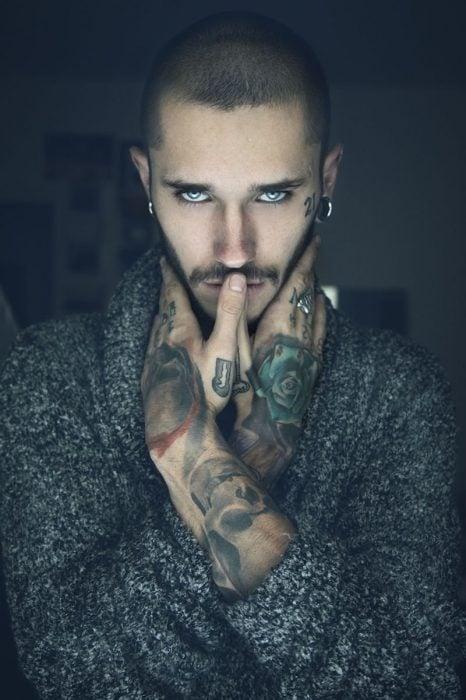 hombre de ojos azules con tatuajes y un aire misterioso