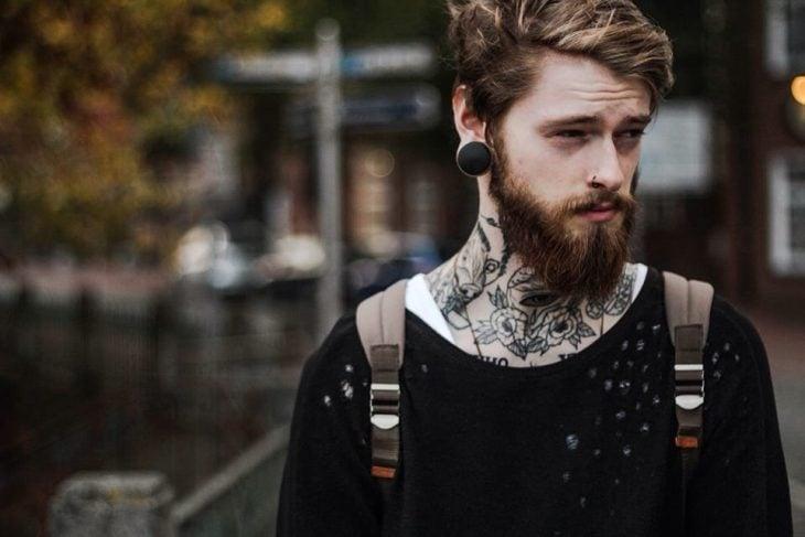 hombre tierno con tatuaje y perforaciones