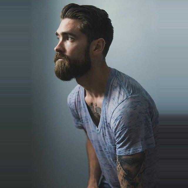 Hombre con barba y tatuajes en los brazos viendo algo