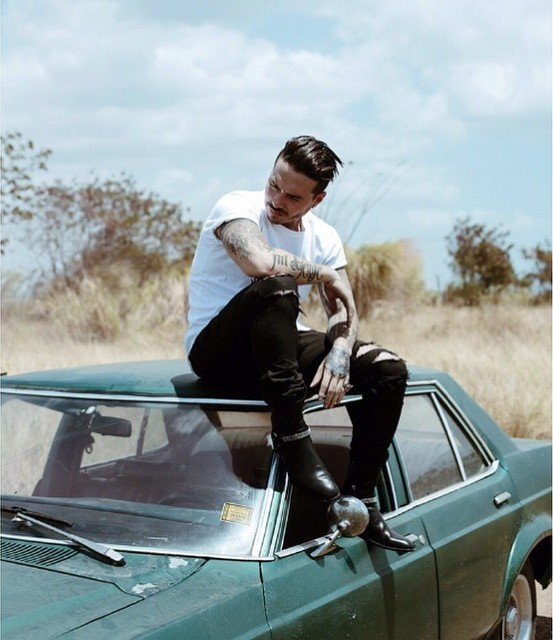 Hombre hipster con tatuajes arriba del techo de un carro