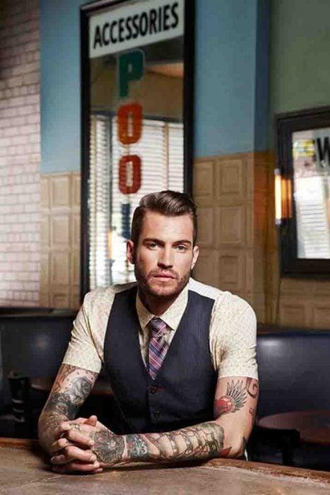 Hombre con camisa corta luciendo sus tatuajes