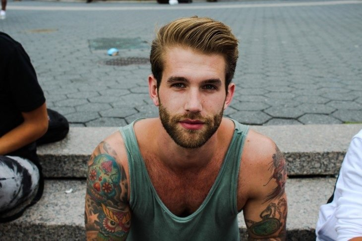Chico atractivo con tatuajes en los brazos