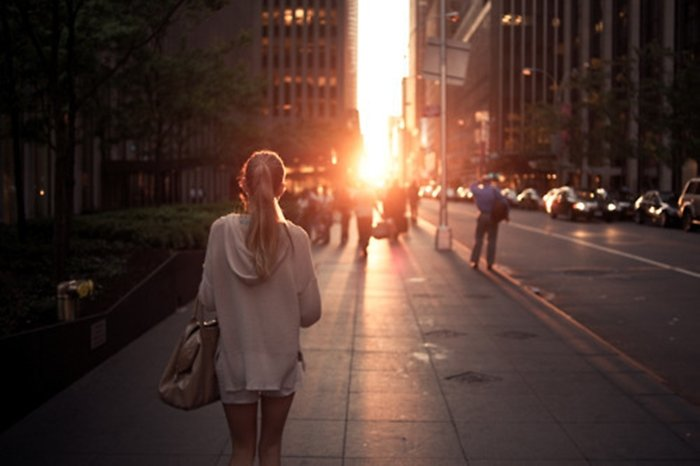Mujer alejándose en la ciudad mientras se pone el sol entre edificios