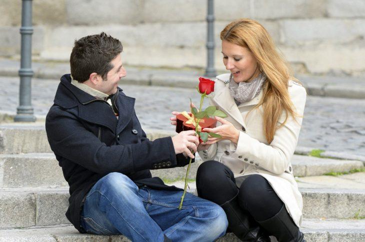 Hombre sentado junto a su novia y entregándole una rosa roja