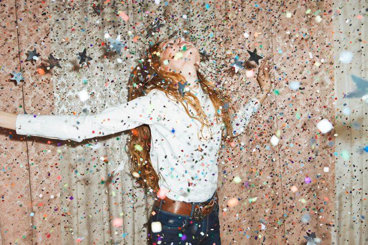 Mujer feliz bajo estrellas de papel