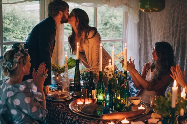 Novios besándose a la luz de la velas mientras les aplauden