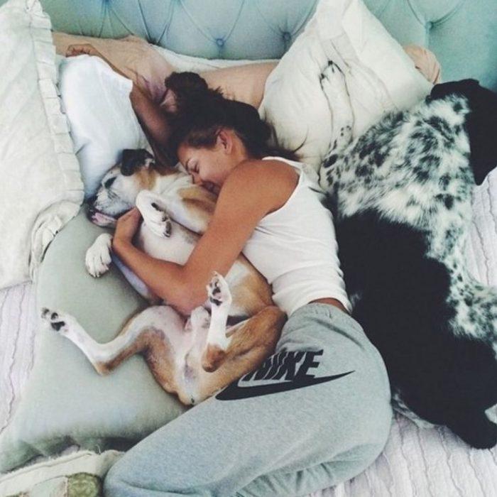 Chica acostada con sus perros