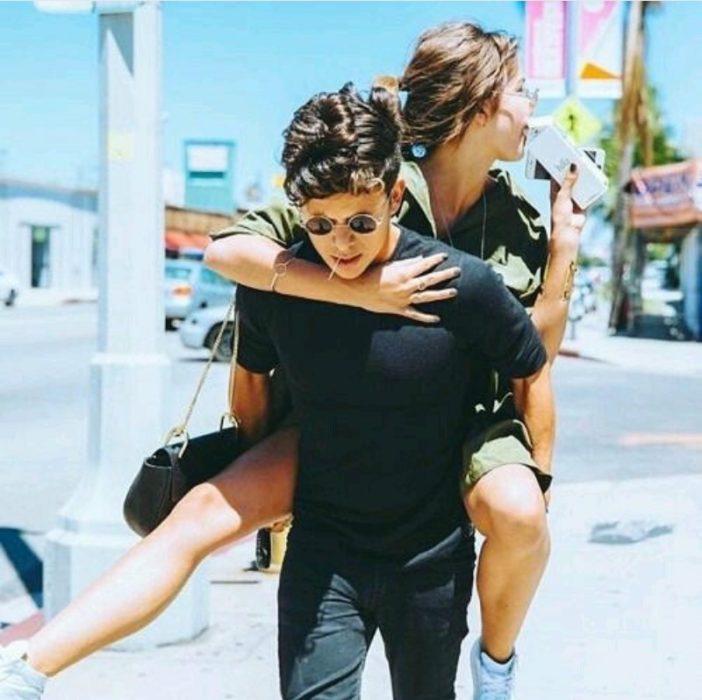Chico carga a chica en la espalda