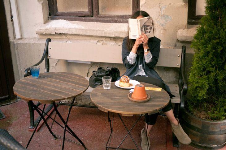 Chica sentada en una banca leyendo