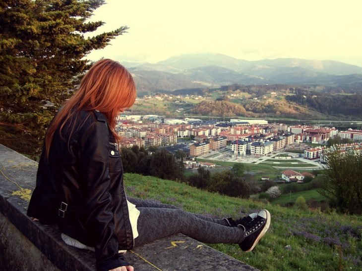 Chica de cabello rojo  sentada en un parque observando la ciudad