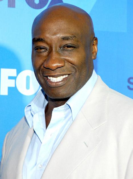 hombre de piel negra usando saco y camisas blancas mientras sonríe posando para una foto