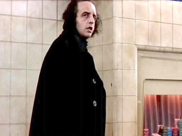 hombre usando un abrigo largo de color negro parado observando algo