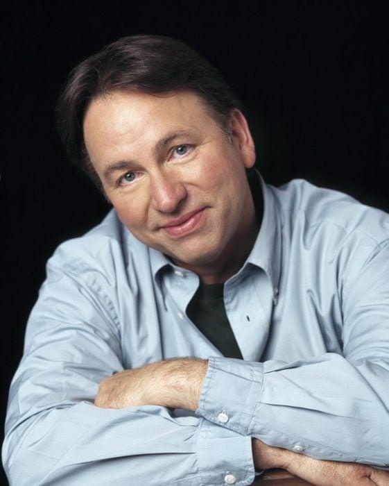 hombre usando una playera de color azul mientras tiene los brazos cruzados y sonríe recargado en un banco