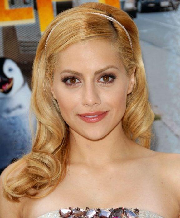 mujer rubia con una diadema en el cabello sonriendo y posando para una foto
