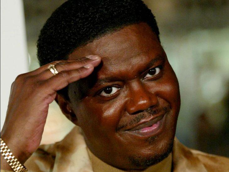 hombre de piel negra usando un saco color dorado mientras saluda con su mano en la cabeza