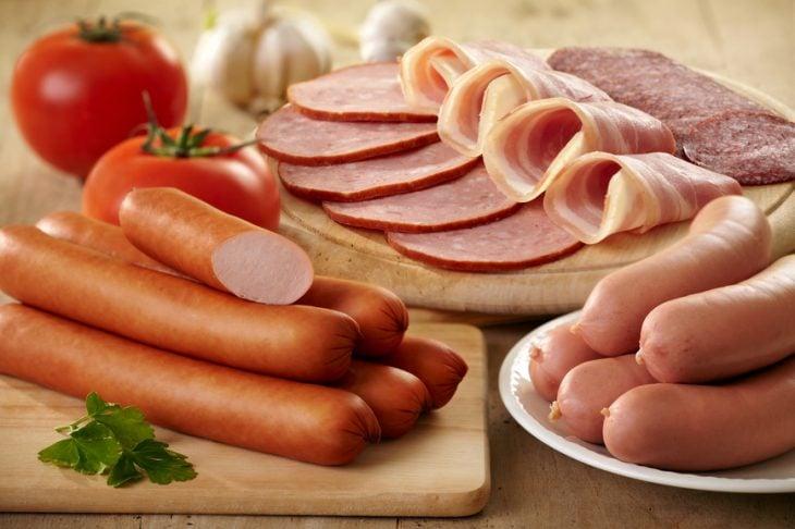 embutidos cortados en una tabla acompañados de tomate o jitomates