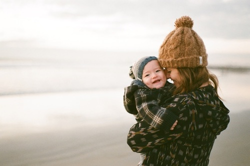mujer sonriendo abrazando a su bebé