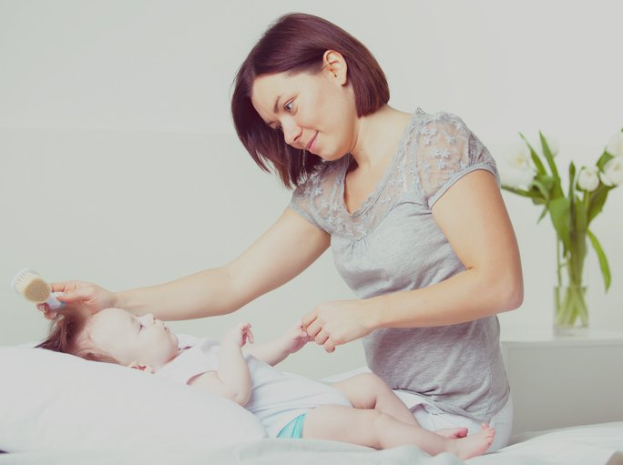 mamá peinando a su bebé
