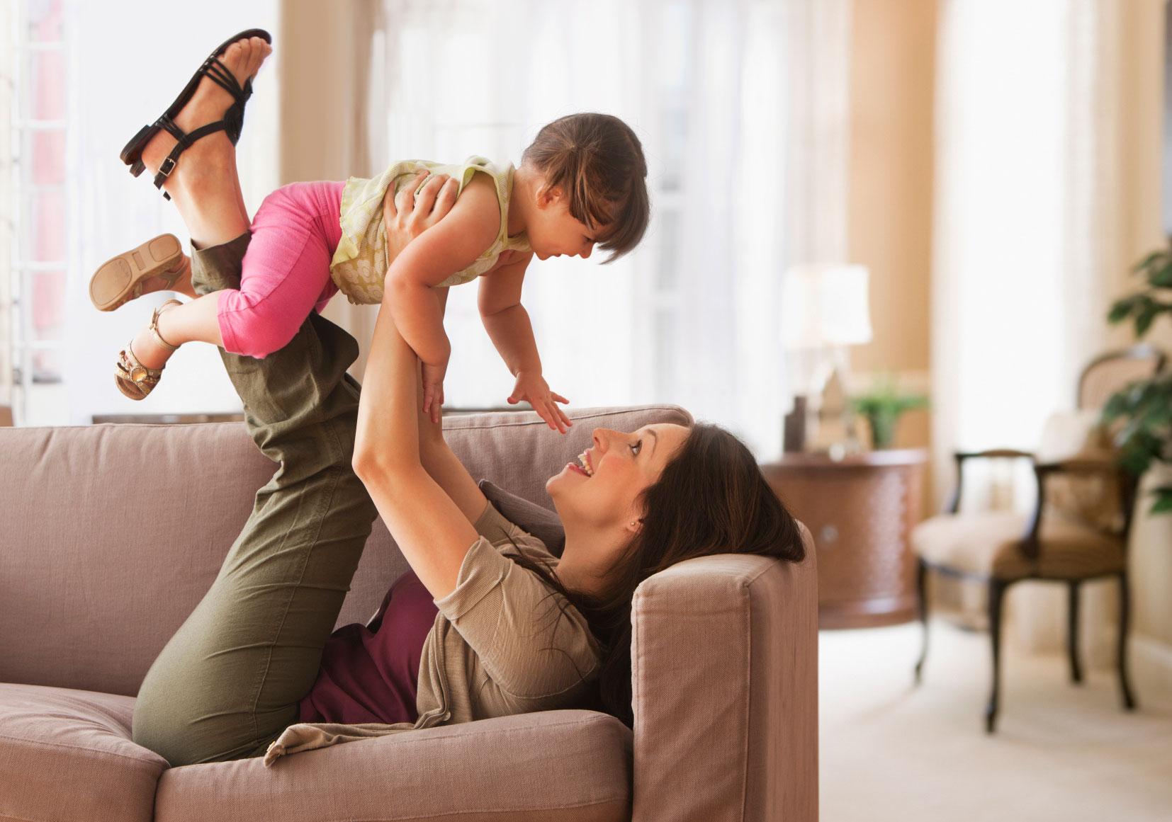 mamá jugando con su hija cargandola en brazos