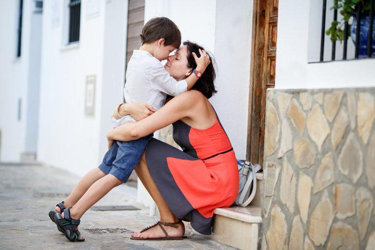 madre e hijo abrazados sentados en el escalón de una casa