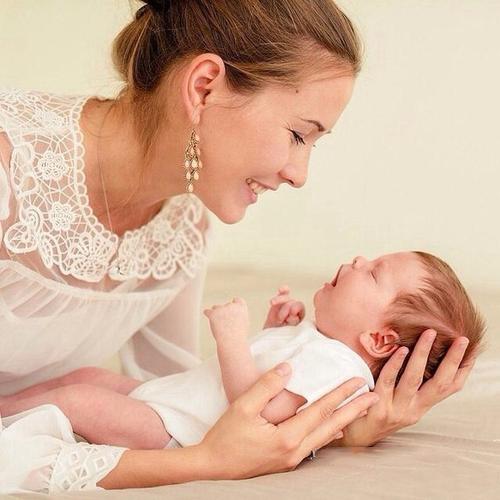 mujer sonriendo sosteniendo a su hijo recién nacido
