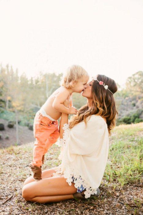 mama sentada en el pasto abrazando a su hijo