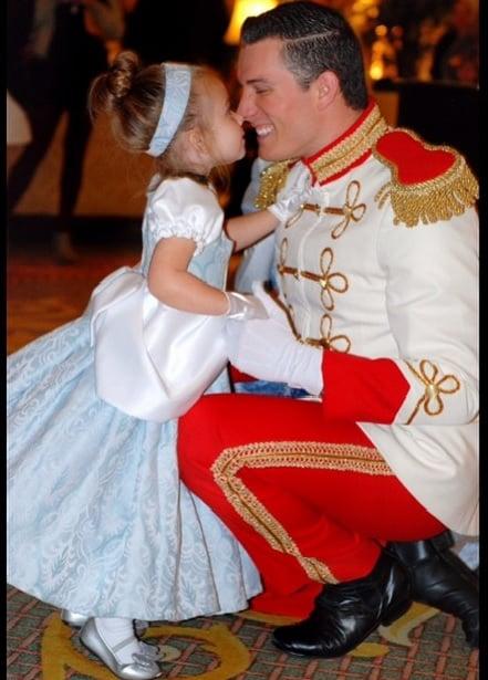 niña vestida de cenicienta besando al príncipe
